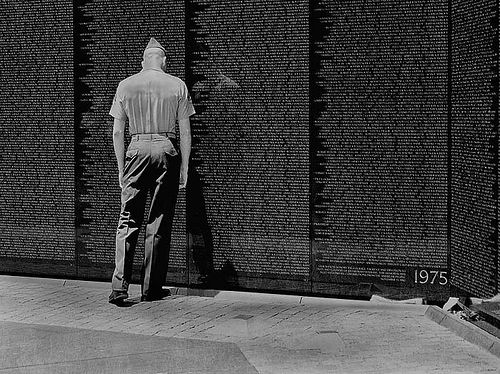 A black and white photo in which one light-skinned US Marine in uniform leans against the Vietnam memorial wall.