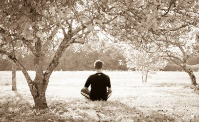 An individual meditates in a field with trees.