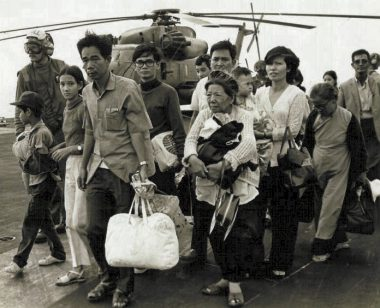 Black-and-white photo of Vietnamese refugees carrying their belongings in front of a helicopter.