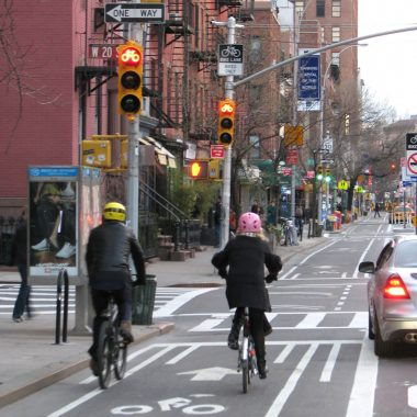 Viewed from behind, 2 people ride bicycles along New York City's new, wide, physically-separated 9th Avenue bicycle lane.
