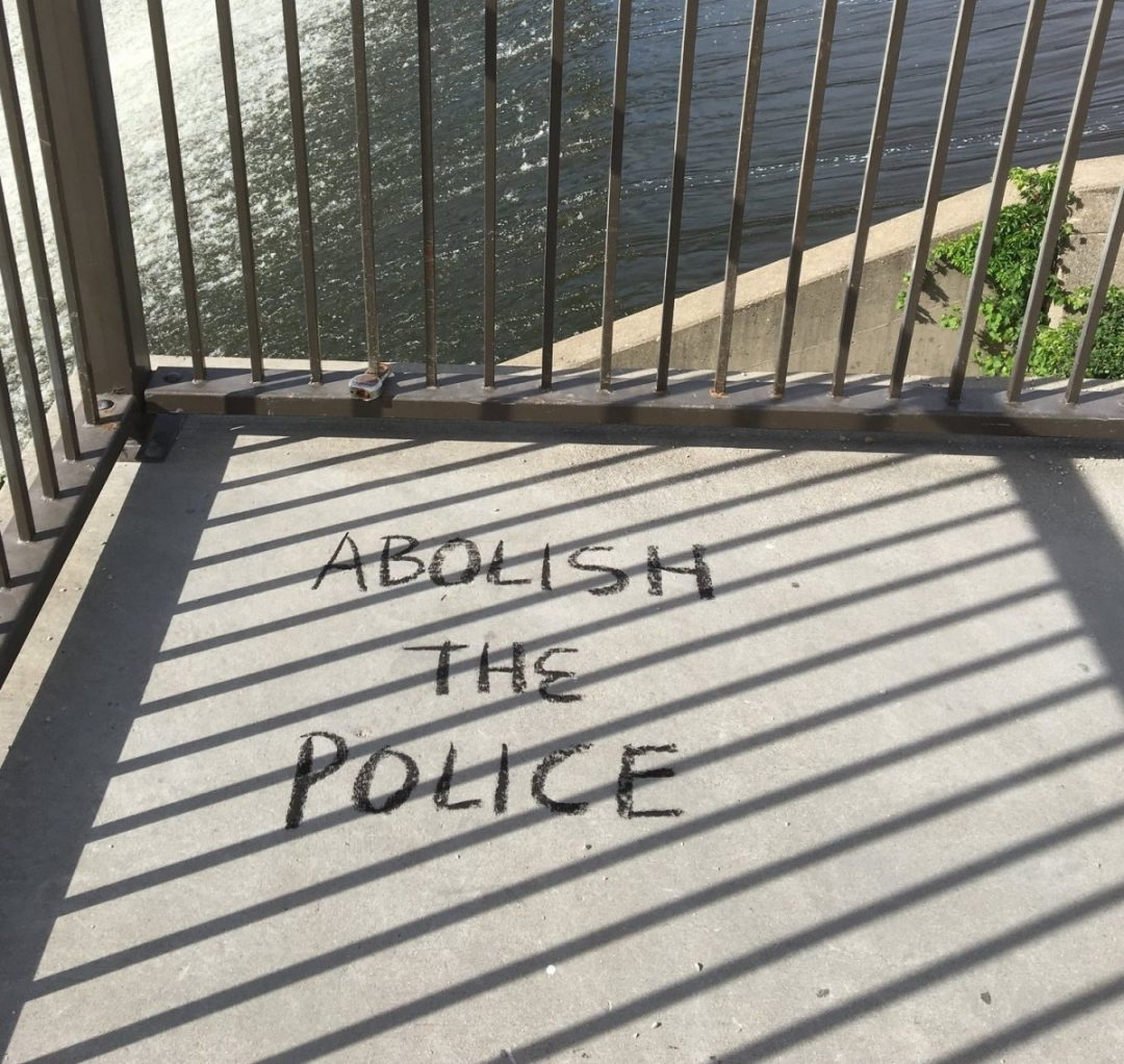 """The words """"Abolish the Police"""" written on the concrete ground."""