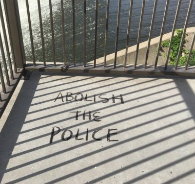 "The words ""Abolish the Police"" written on the concrete ground."